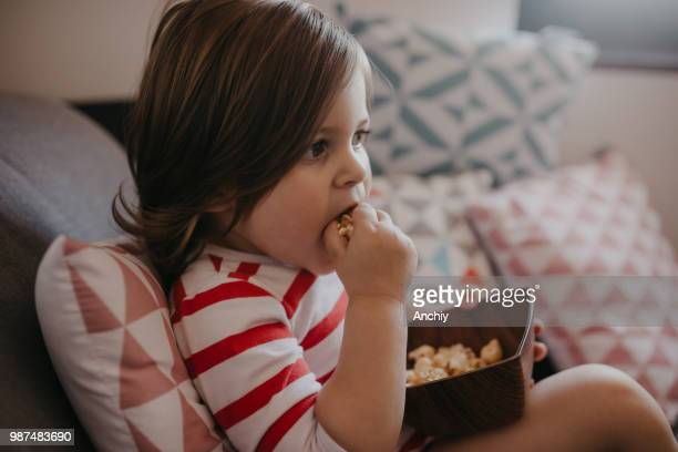 Cute little girl eating popcorn and watching cartoons