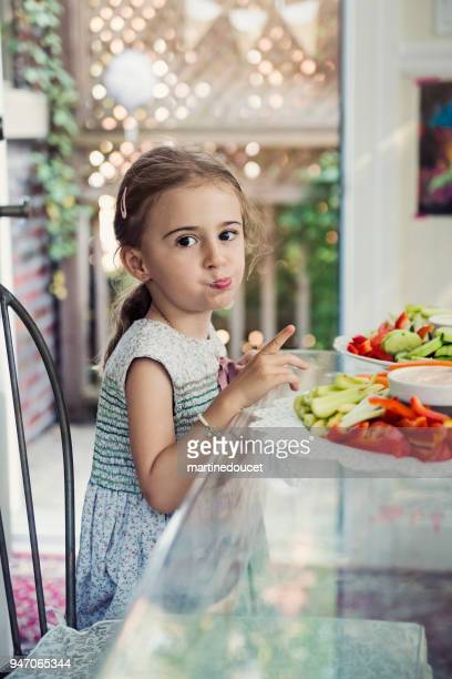 Cute little girl eating raw vegetables at a buffet.