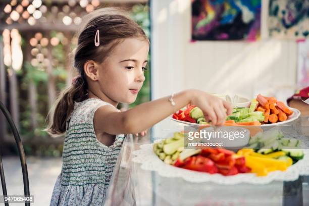 Niña linda comer verduras crudas en un buffet.