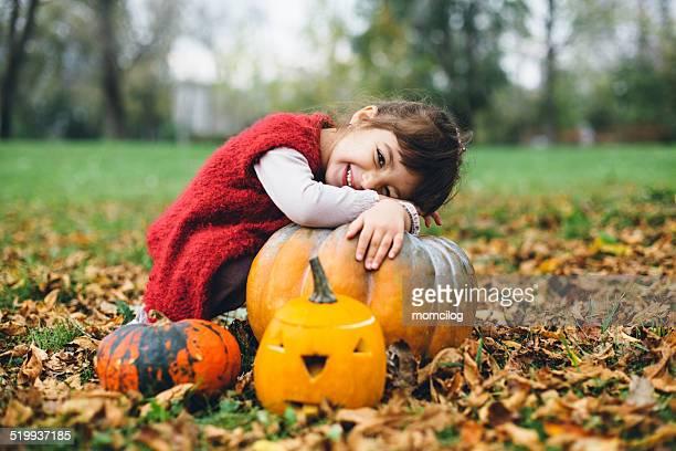 Niedliche kleine Mädchen umarmen Kürbis