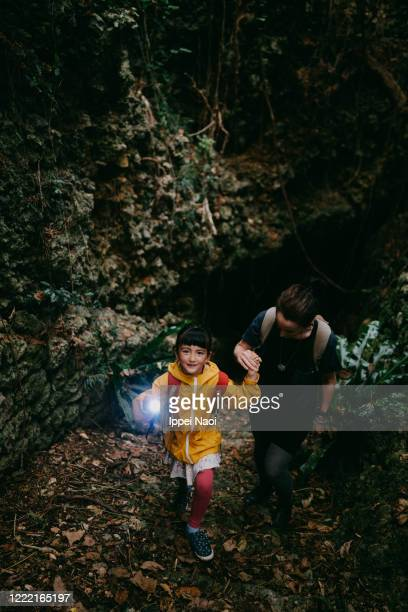 cute little girl exploring cave with flashlight, okinawa, japan - ippei naoi stock pictures, royalty-free photos & images