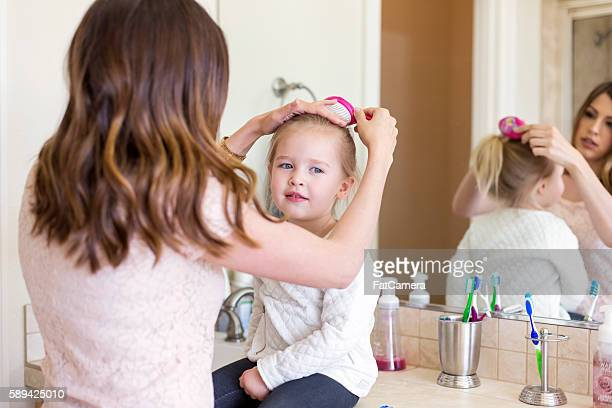 Cute little girl getting her hair brushed by mom