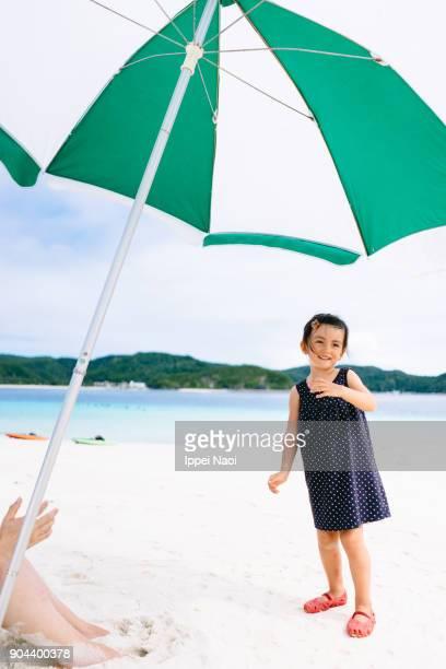 Cute little girl having fun on white sand tropical beach under parasol