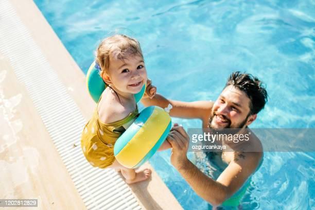 petite fille mignonne ayant l'amusement avec des parents dans la piscine - piscine photos et images de collection