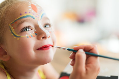 Cute little girl having her face painted for Halloween party. Halloween or carnival family lifestyle background. Face painting, headshot close up. 1038671488