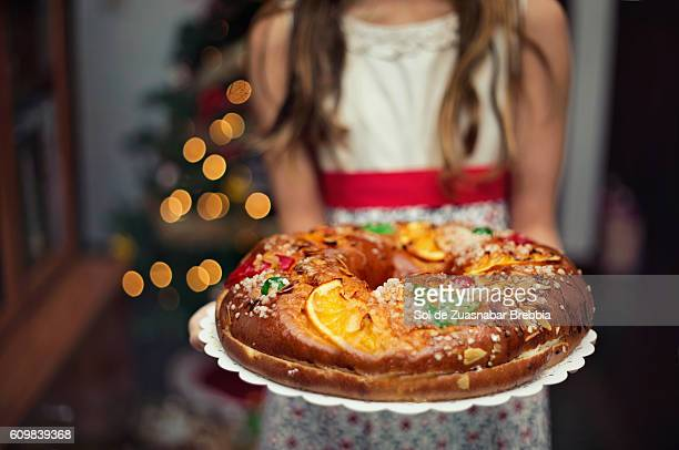 cute little girl holding a christmas sweet at home. - fruit cake stock pictures, royalty-free photos & images