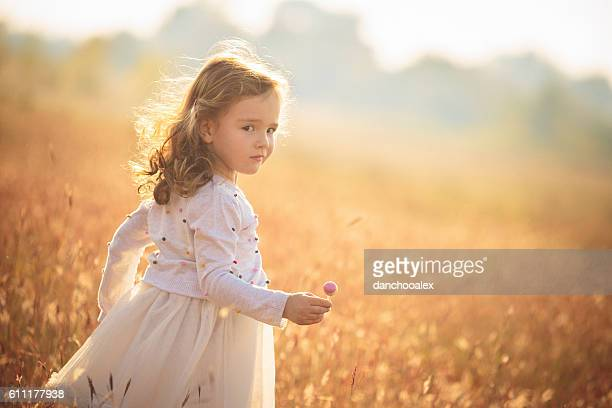 Cute little girl holding lollipop outdoors in nature