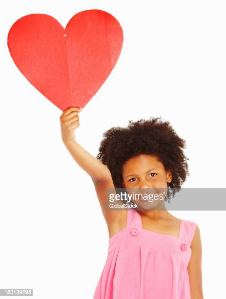 Cute little girl holding up a heart shape against white