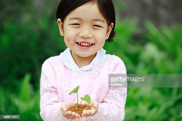Süßes kleines Mädchen hält mit Setzling