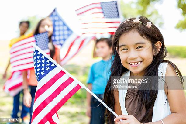cute little girl holds american flag - patriotic stock pictures, royalty-free photos & images