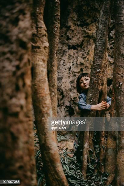 Cute little girl hugging banyan roots