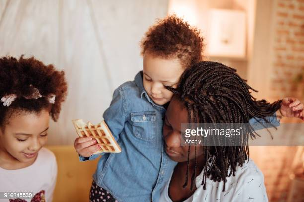 かわいい女の子彼女の母を抱き締めると彼女の髪で遊んで - interracial cartoon ストックフォトと画像