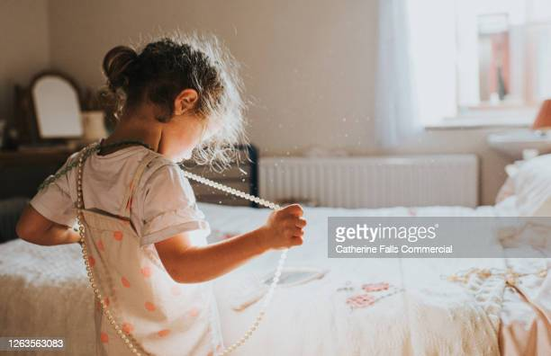 cute little girl in a dated bedroom tries on costume jewellery - girls stock pictures, royalty-free photos & images