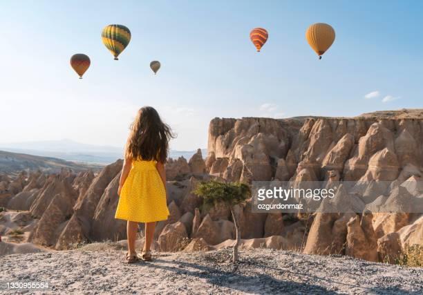 カッパドキア、トルコで熱気球を見て黄色のドレスを着たかわいい女の子 - ネヴシェヒル県 ストックフォトと画像