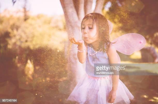 Mignonne petite fille en costume de fée soufflant des paillettes dans le parc