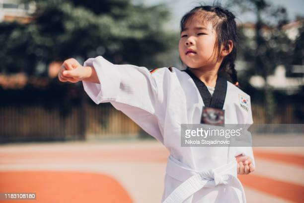 cute little girl in kimono training karate punch - one girl only stock pictures, royalty-free photos & images