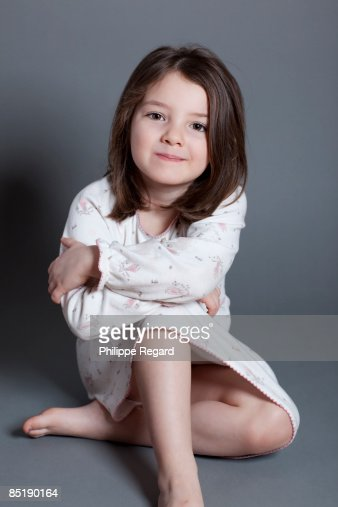 Cute Little Girl In Nightdress Smiling At Us Stock Photo