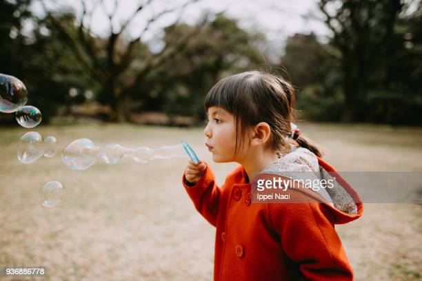 Cute little girl in red coat blowing bubbles in park