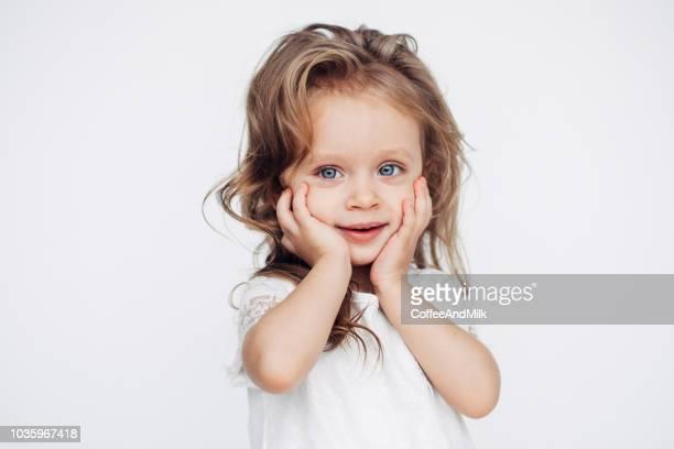 cute little girl in white dress smiling on camera - girls foto e immagini stock