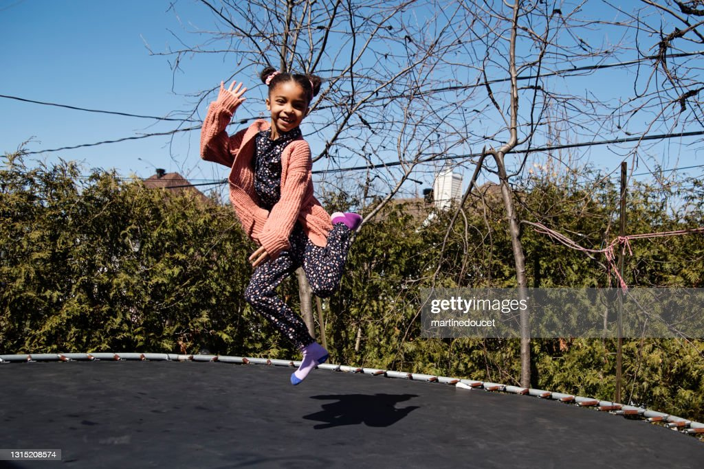 Cute little girl jumping on trampoline outdoors in springtime. : Stock Photo