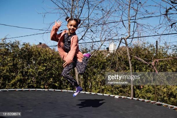"""nettes kleines mädchen springt auf trampolin im freien im frühling. - """"martine doucet"""" or martinedoucet stock-fotos und bilder"""