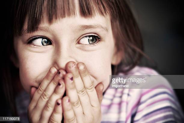 Cute little girl laughing and covering mouth