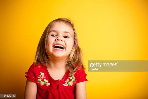 Cute Little Girl Laughing While on Yellow Background