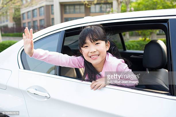 Cute little girl leaning out of car window and waving