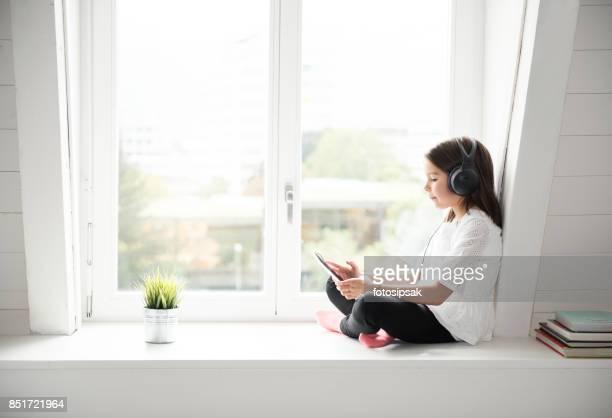 Schattig klein meisje, luisteren naar muziek met digitale tablet thuis