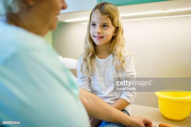 Mignonne petite fille regardant grand-mère dans la cuisine alors qu'elle prépare des aliments