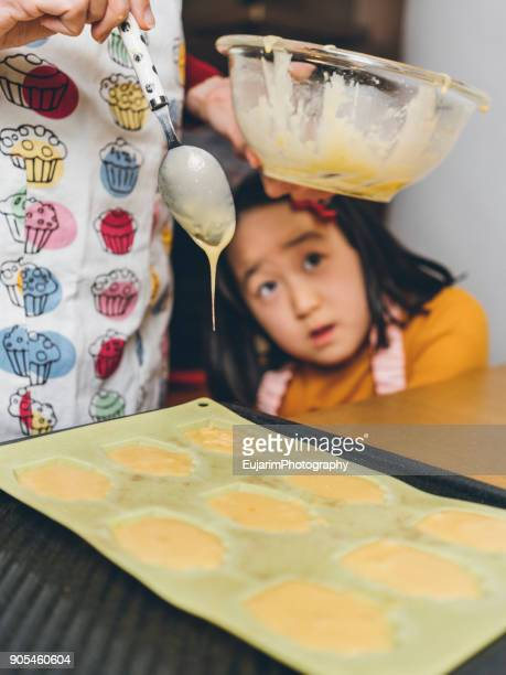 Cute little girl looking at her mother making madeleines