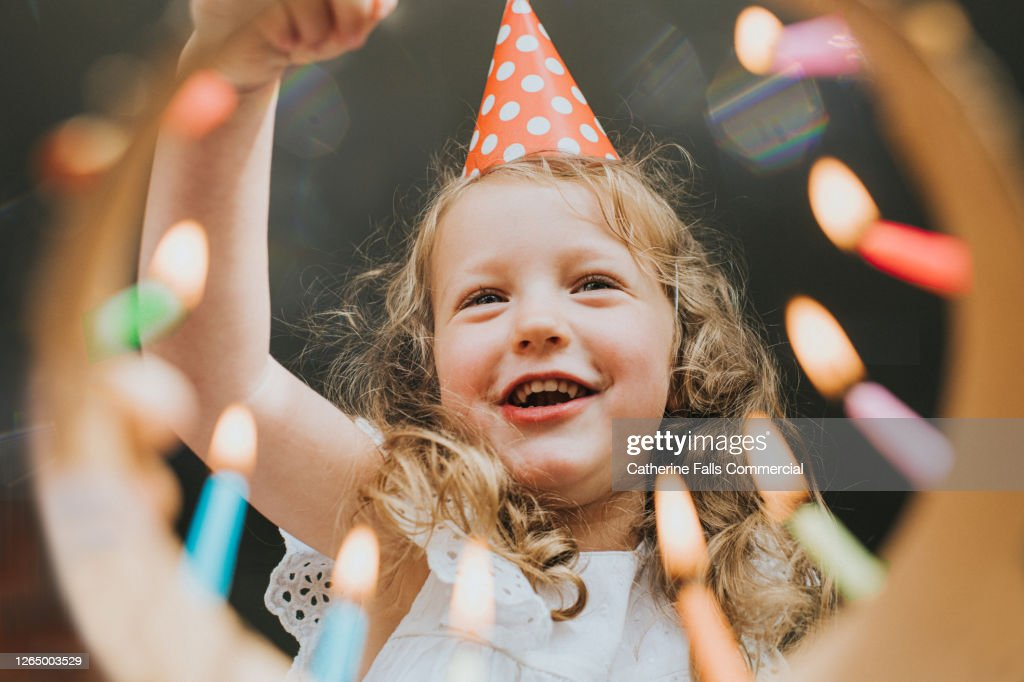 Cute little Girl looking down at a Birthday cake, about to blow out the candles. : Stock Photo