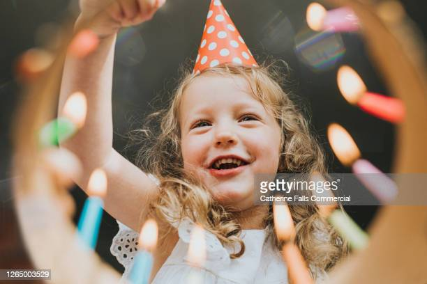 cute little girl looking down at a birthday cake, about to blow out the candles. - candle stock pictures, royalty-free photos & images
