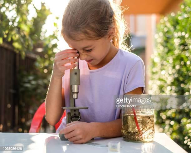 Schattig klein meisje kijkend naar de Microscoop