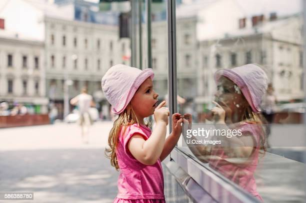 Cute Little Girl Looking to The Window of a Store