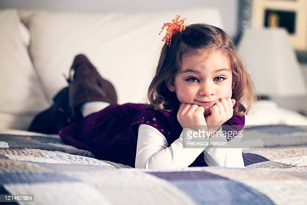 cute little girl lying on bed - rebecca nelson stock pictures, royalty-free photos & images