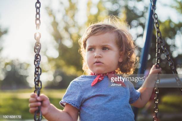 Cute little girl on a swing at playground
