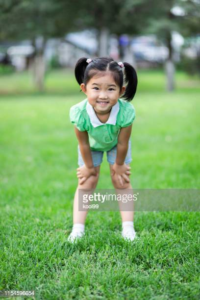cute little girl on the lawn - hand on knee stock pictures, royalty-free photos & images