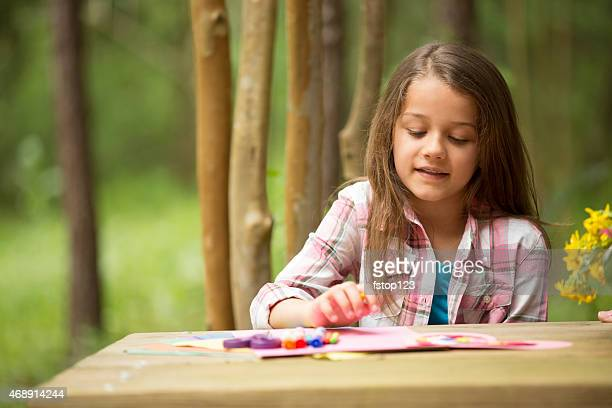 Cute little girl outdoors making Father's Day card. Child, backyard.