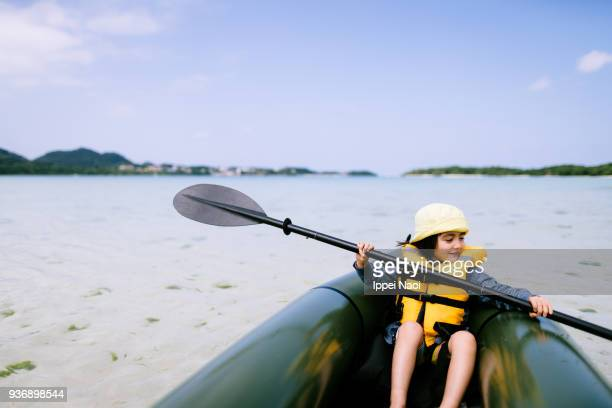 Cute little girl paddling inflatable raft on shallow tropical water