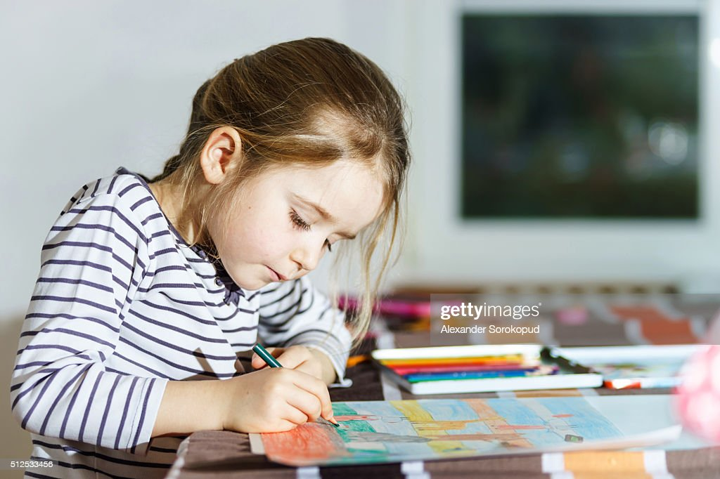 Cute little girl painting by colorful pencil at home : Stock-Foto