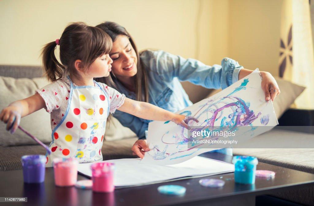carino bambino pittura con mamma insieme a casa, ritratto di madre e figlia pittura a casa : Foto stock