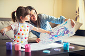 cute little girl painting with mommy together at home, portrait of mother and daughter painting at home