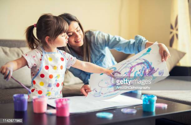 cute little girl painting with mommy together at home, portrait of mother and daughter painting at home - dipinto foto e immagini stock