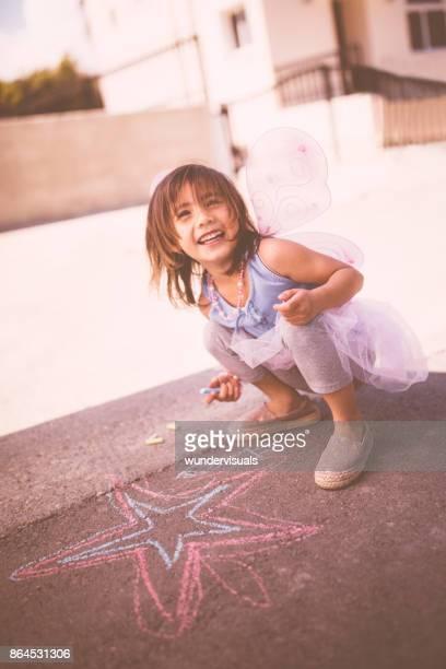 Mignonne petite fille jouant et dessin à la craie à l'extérieur