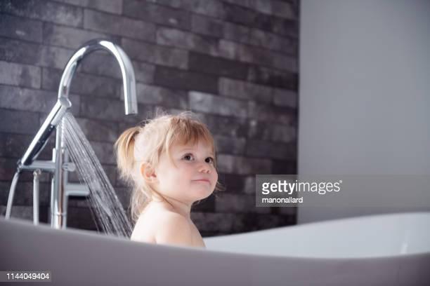 petite fille mignonne jouant dans une baignoire - fille sous la douche photos et images de collection