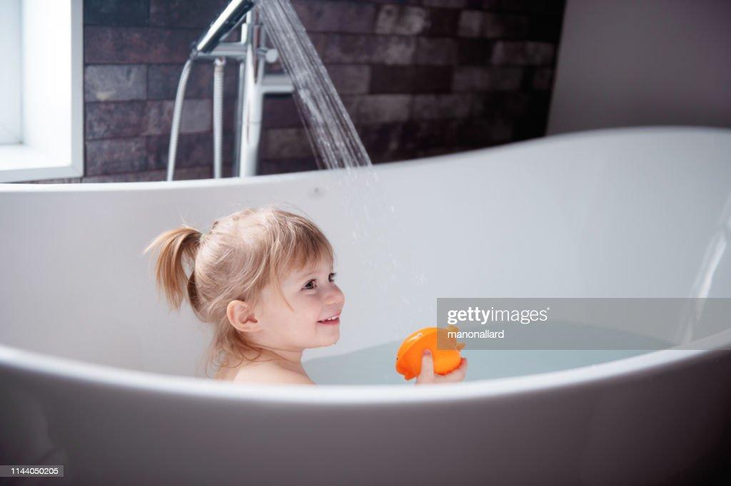 かわいい女の子が浴槽で遊んで : ストックフォト
