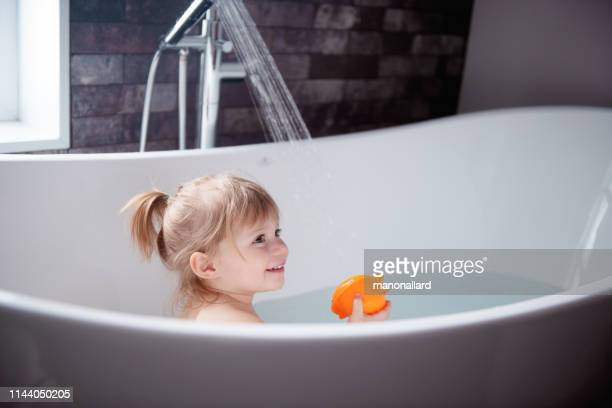 cute little girl playing in a bathtub - bathtub stock pictures, royalty-free photos & images