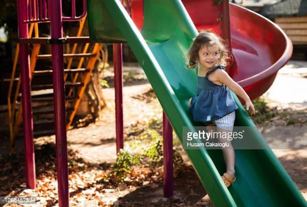 menina bonita brincando no escorregador no parque. - olhos azuis - fotografias e filmes do acervo