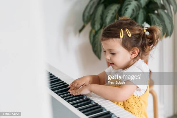cute little girl playing piano - serbia stock pictures, royalty-free photos & images
